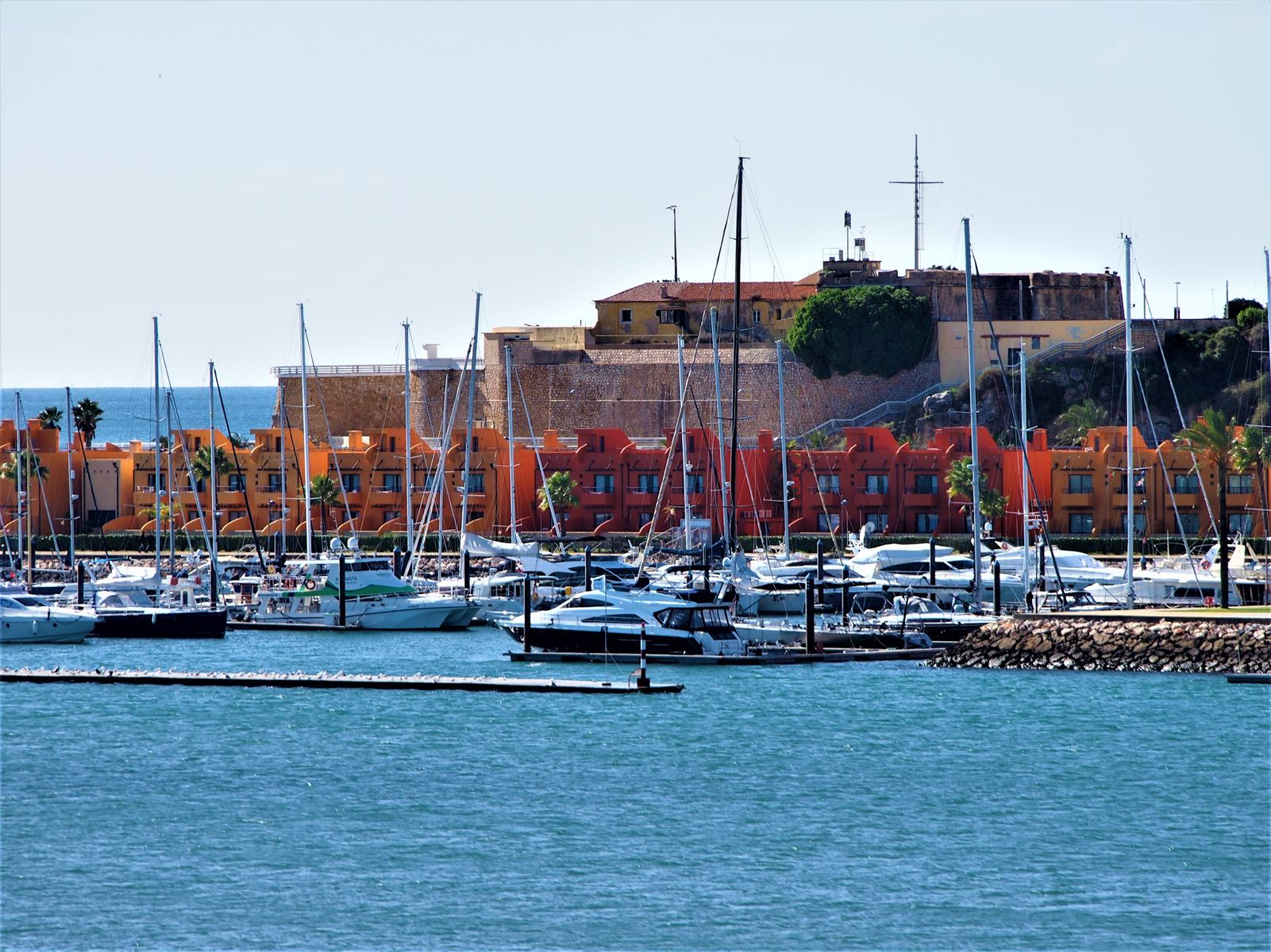 Looking towards Portimao showing the marina, the brightly coloured buildings of Tivoli Marina hotel and behind is the Fort of Santa Catarina.