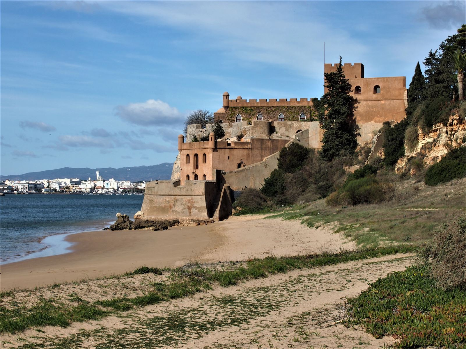 The castle of São João do Arade, now privately owned with Praia Grande in the foreground at Ferragudo.