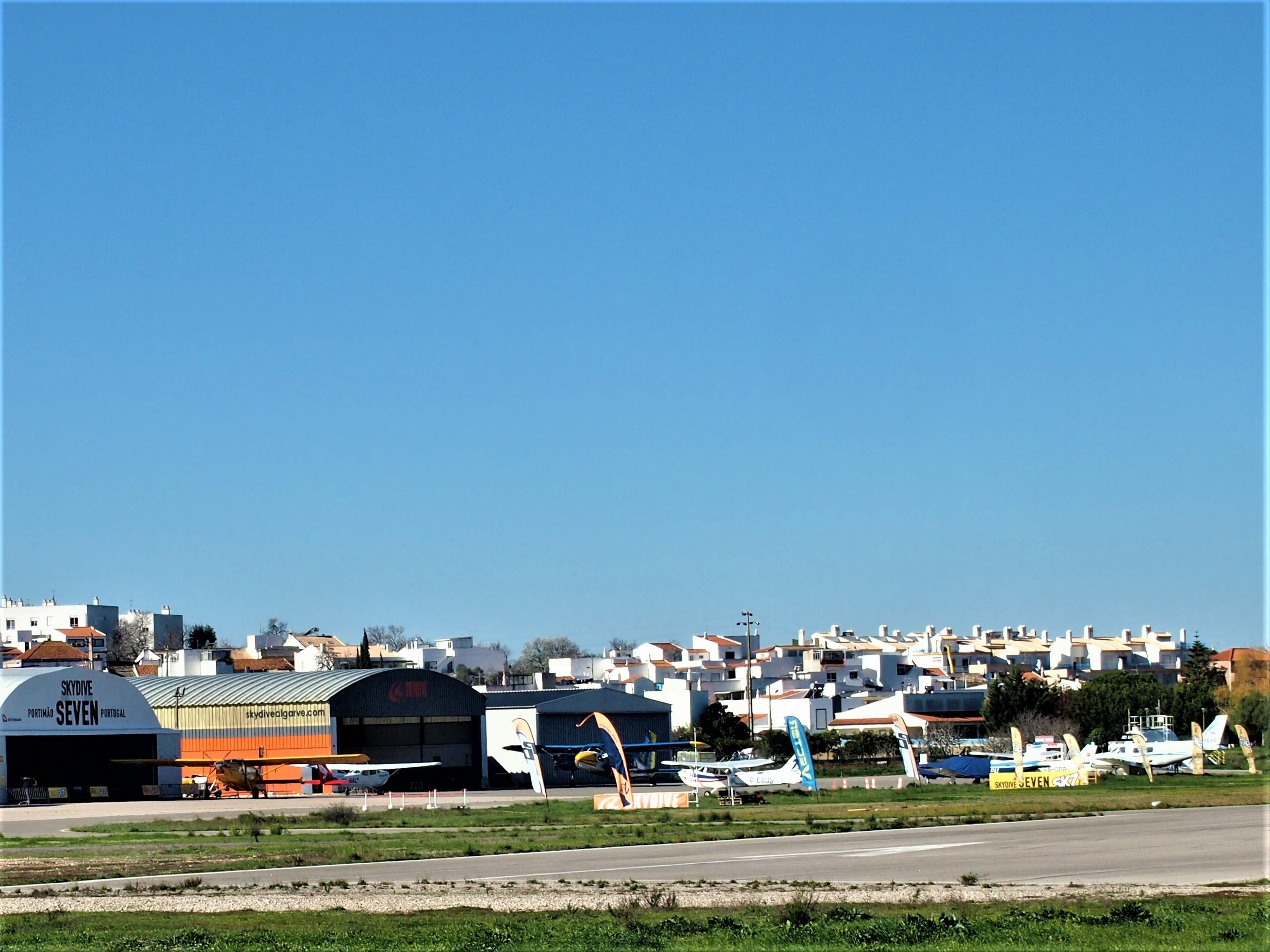Alvor aerodrome or Portimão airport - airport code is PRM. Take a scheduled flight to Cascais, Lisbon