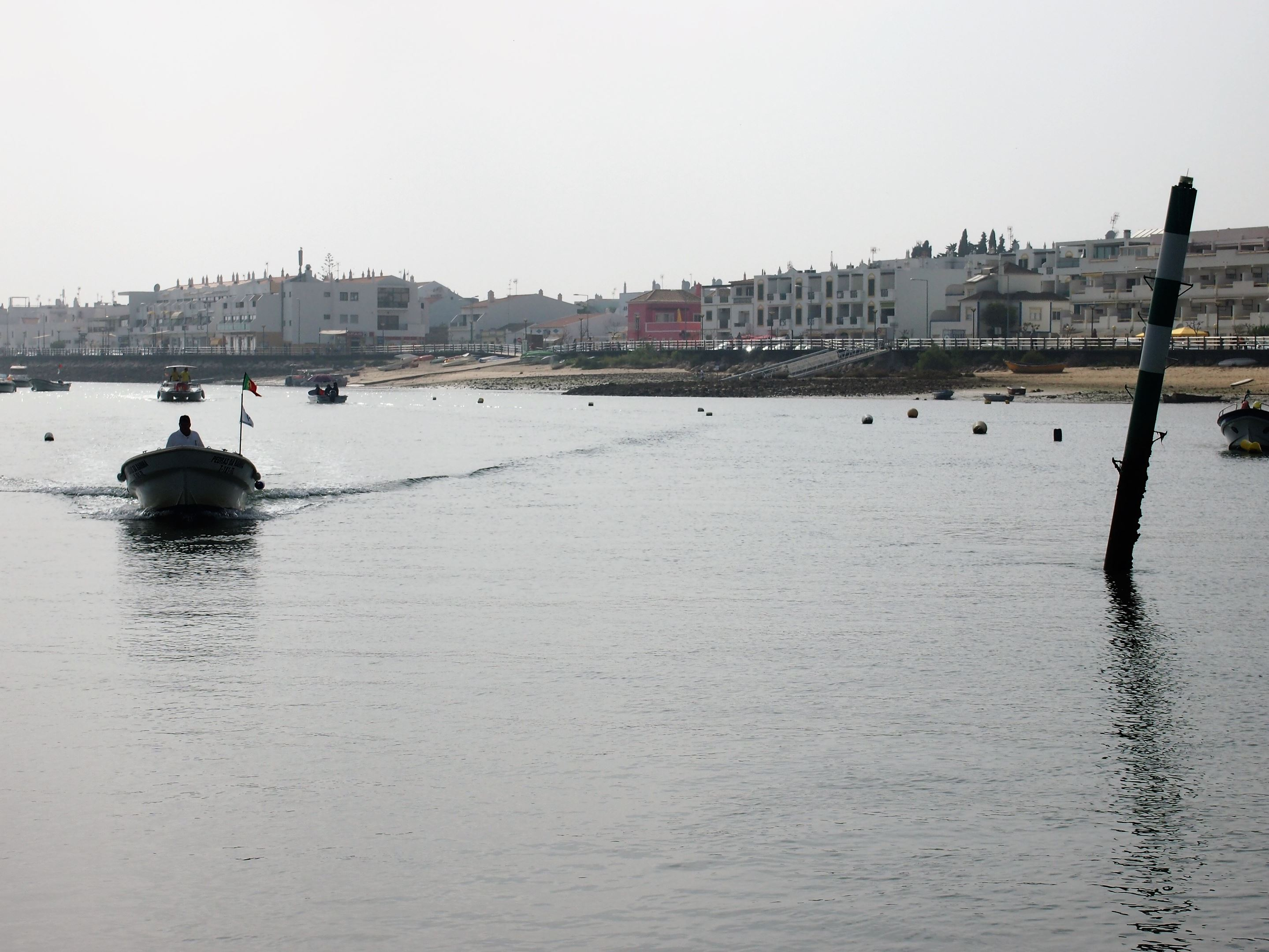 A small ferry boat on its way to Ila de Cabanas with Cabanas de Tavira in the background