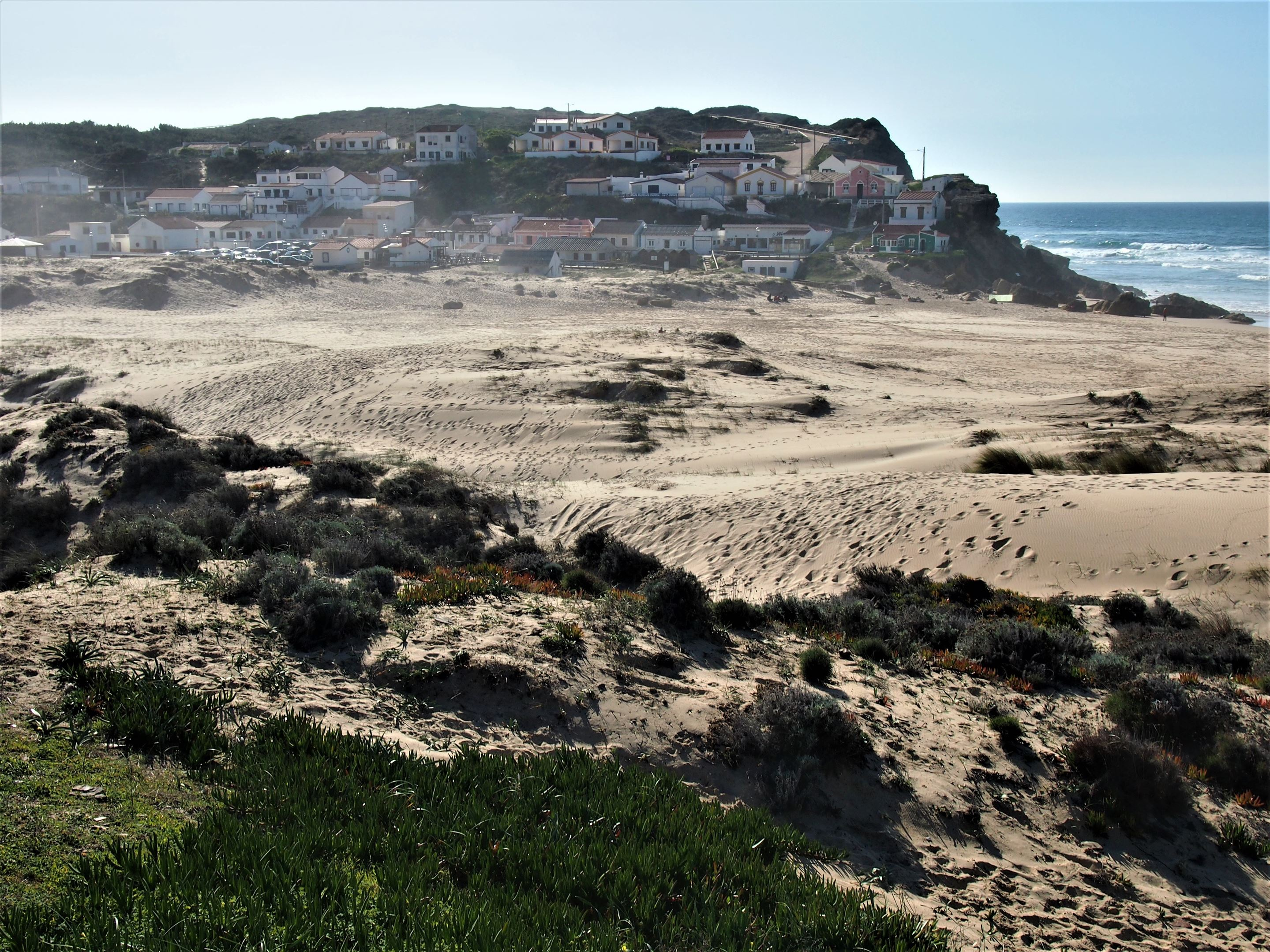Praia do Monte Clérigo, con su pequeño pueblo en el fondo, Aljezur