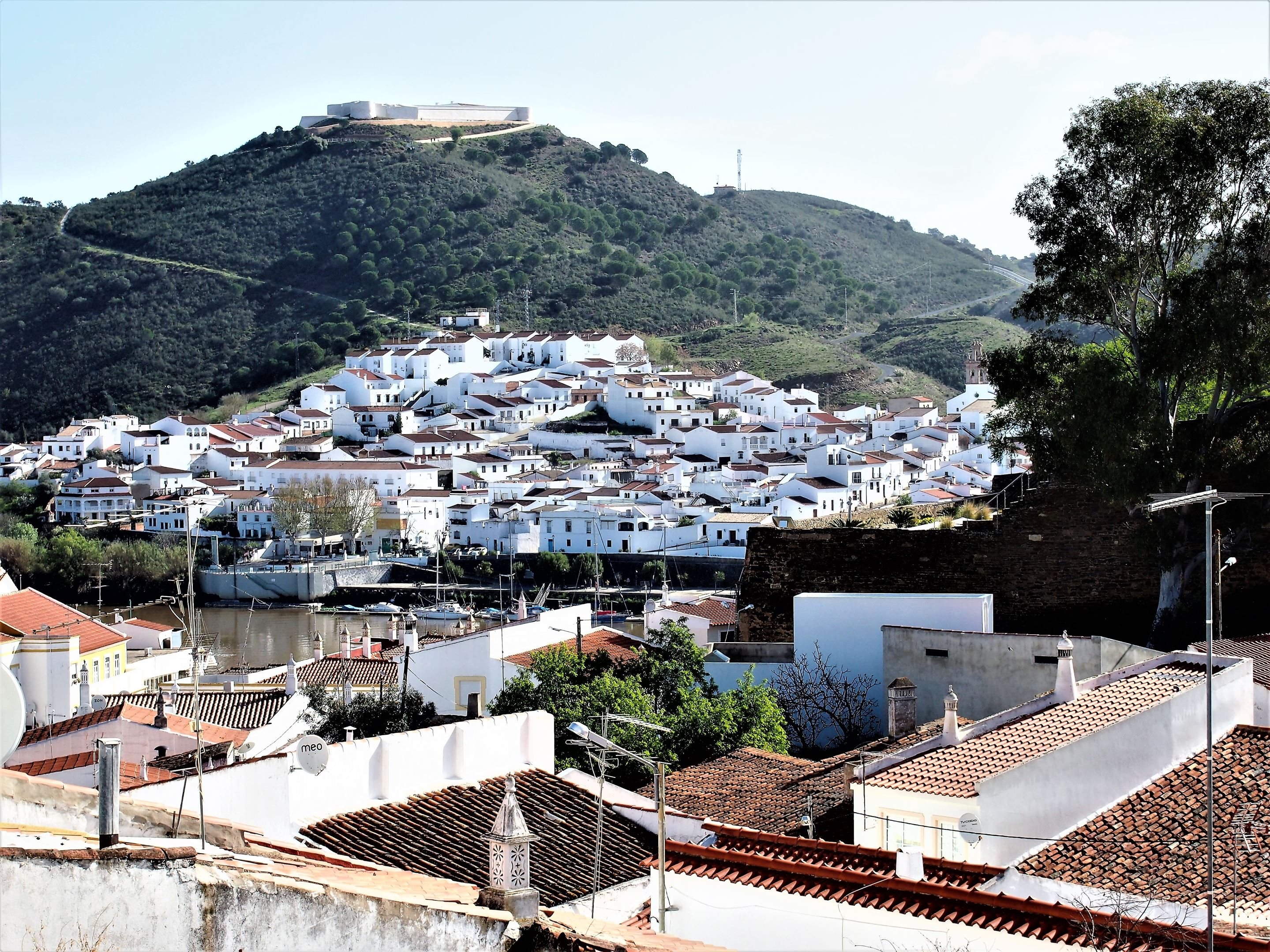 Looking across the rooftops of Alcoutim in Portugal to Sanlúcar de Guadiana in Spain with the castle at the highest point.