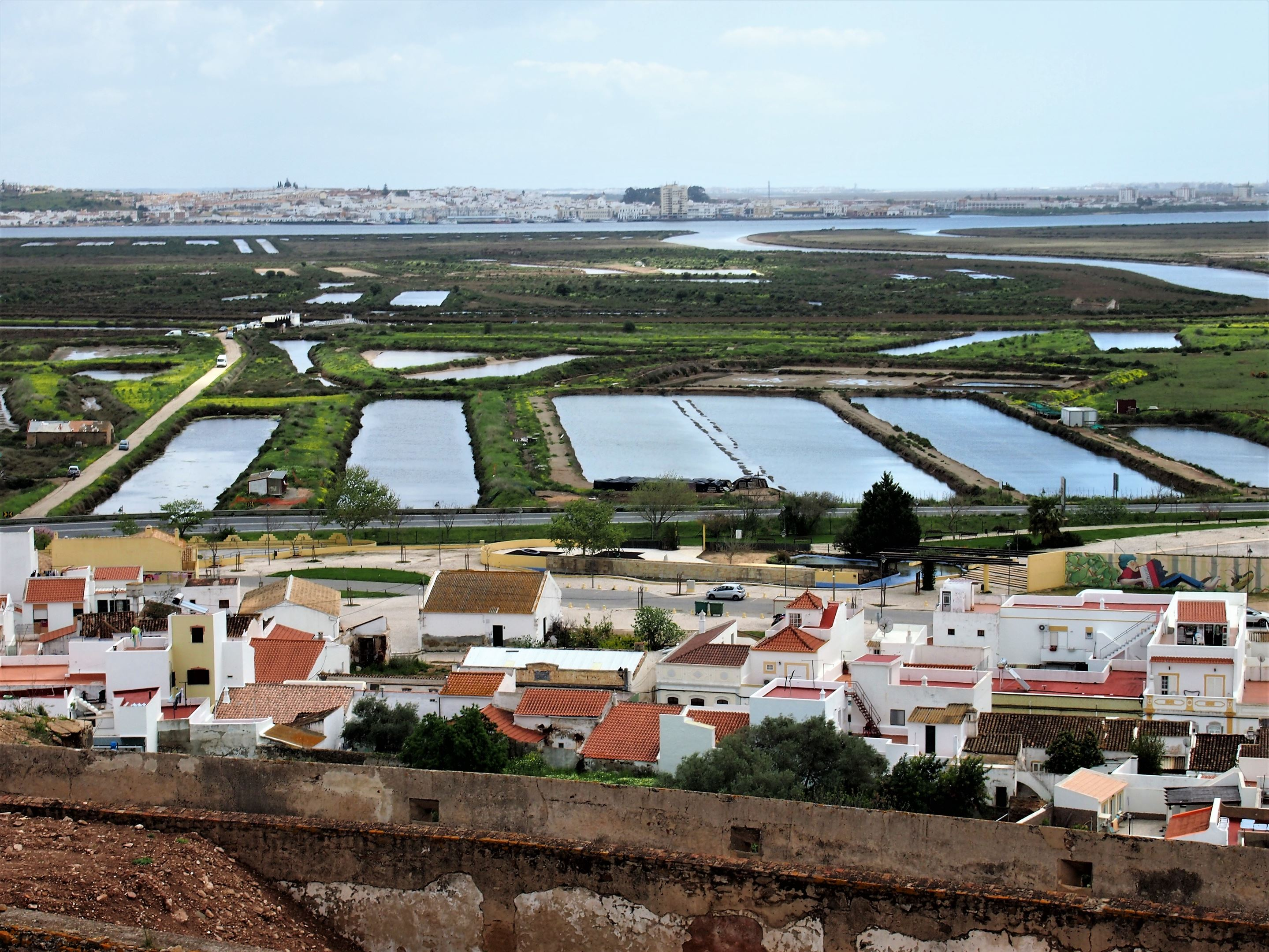 A vista do Castelo de Castro Marim, com Castro Marim em primeiro plano, as salinas, o rio Guadiana e no topo, Ayamonte, em Espanha.